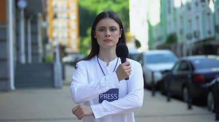 odznaka : Serious female journalist with microphone and press badge looking at camera, TV