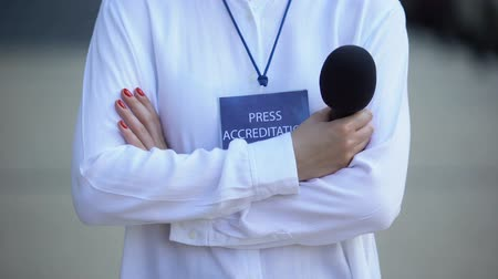 mensen massa : Woman with microphone and press accreditation badge, media pass for journalist