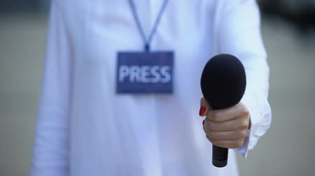 odznaka : Journalist with press id proposing microphone for interview, television news