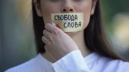 taboo : Woman taking off tape with freedom of speech phrase in russian over mouth