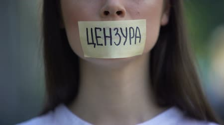 taboo : Woman resolutely taking off tape with censored word in russian over mouth