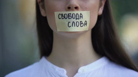 taboo : Freedom of speech phrase in russian over female taped mouth, democracy concept Stock Footage