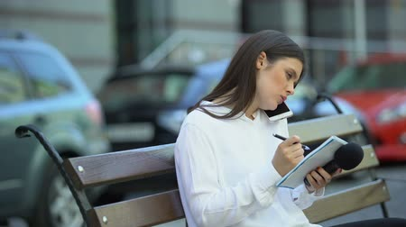 mensen massa : Female journalist making notes and talking phone, preparing for reportage