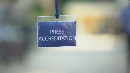 odznaka : Press accreditation pass against blurred background, media ID card during event