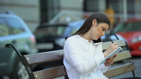 freio : Businesswoman talking phone sitting on bench, making notes during conversation