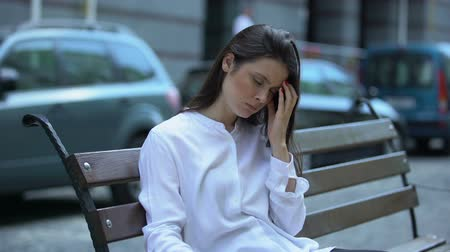片頭痛 : Exhausted woman sitting on bench, suffering from migraine pain, health problem 動画素材