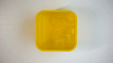 litter box : Yellow litter-bin full of disposable plastic cups, utilization, stop motion