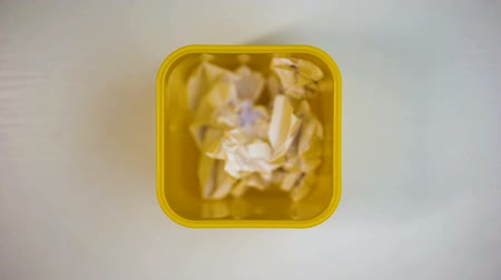 crumpled : Overflowing waste paper in yellow garbage bin, recycling concept, stop-motion