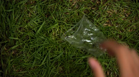ekosistem : Human hand throwing crumpled plastic cup on lawn environmental pollution problem