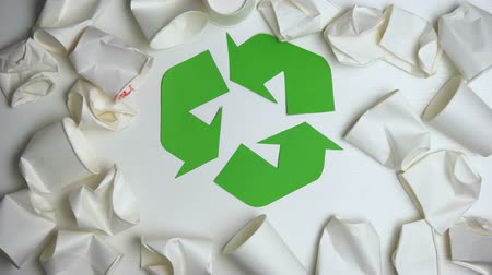 preservation : Crumpled disposable paper cups lying around circling recycling sign, save nature Stock Footage