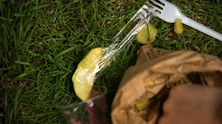 irresponsible : People hands throwing litter on grass after picnic, nature neglect, pollution