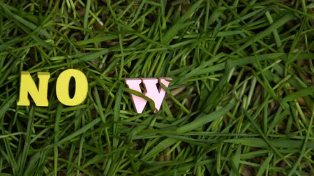 fráze : No waste letters appearing on green grass, protest against single-use plastic
