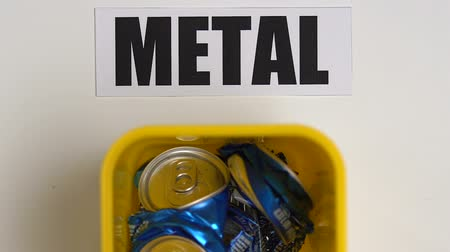 litter box : Person putting crumpled cans into plastic container near metal sign, recycling
