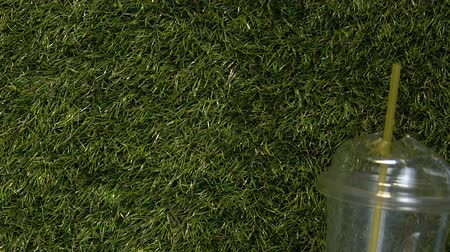 discard : Wind blowing disposable plastic cap thrown on green grass, ecological problem