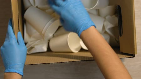 poluir : Hands in gloves checking box with cellulose used cups, recycling factory Stock Footage