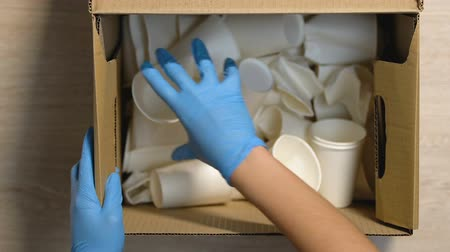 influence : Hands giving worker in gloves box with paper cups and cellulose sign, recycling