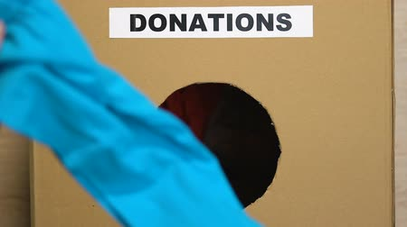 humanitarian : Hand putting old clothes in box with donations sign, charity for poor people Stock Footage