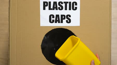 再利用可能な : Hand putting used plastic caps in waste container, sorting center, recycling