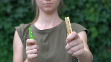 prendedor de roupa : Female proposing wooden clothespin instead of plastic one, eco-friendly item