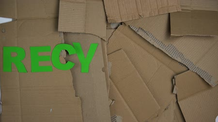 szakadt : Recycling word made of green letters on cardboard background, save planet Stock mozgókép