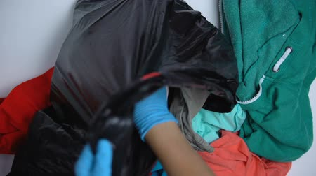 reciclado : Volunteer hand in glove packing used clothing in plastic bag, sorting donations