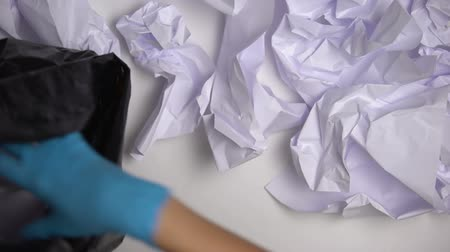 separado : Janitor in gloves collecting paper in office, inefficient material usage, damage