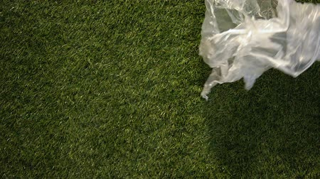 щит : Wind rolling plastic packing on grass, dangerous responsibility towards earth