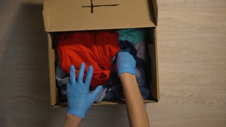 přátelský : Volunteer checking clothes in box helping poor people donating church community