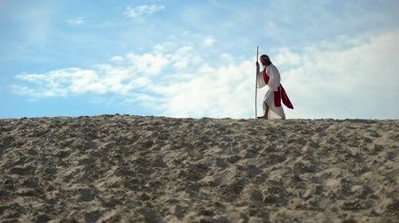 ascetic : Jesus with staff hardly walking in sands, exhausted ascetic fasting to save soul Stock Footage