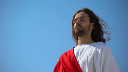fiel : Saint man with closed eyes praying to god on blue sky background, spirituality Stock Footage