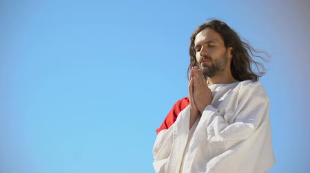 religione ebraica : Man in robe praying to God against blue sky background, asking soul salvation