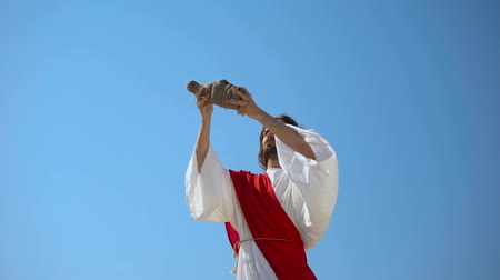 prophète : Jesus raising wine in hands to sky, blessing sacramental Eucharist beverage