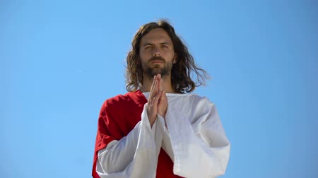 repenting : Jesus in robe praying against blue sky background, asking God to forgive sinners Stock Footage