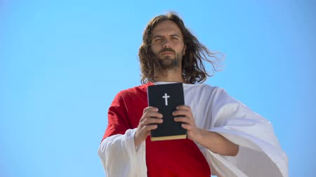 духи : Strict God holding Bible against blue sky, reminding of faith and repentance Стоковые видеозаписи