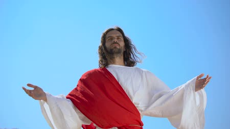 religião : Saint man in robe raising hands to sky, praying for soul salvation, resurrection