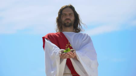 jezus : Man in robe showing sprout against sky, nature saving, environmental problems Wideo