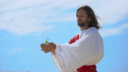 testament : Man like Jesus holding sprout against sky, biblical story of world creation