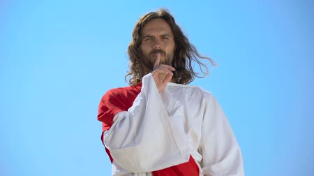 religione ebraica : Jesus showing silence gesture on sky background, speechless prayer, deep faith
