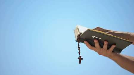 megváltás : Hands holding bible and rosary on blue background, praying to god, template