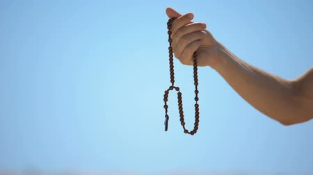 evangelical : Hand holding rosary, praying to god on blue background, religious spirituality Stock Footage
