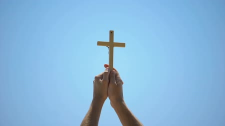 batismo : Male hands raising wooden cross to blue sky, religious conversion, baptism