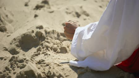 philosopher : Hand in robe pouring sand, concept of passing life, time is fleeting, back view