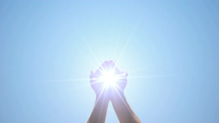 mystik : Hands holding sacred light against blue sky, religious miracle, ray of hope
