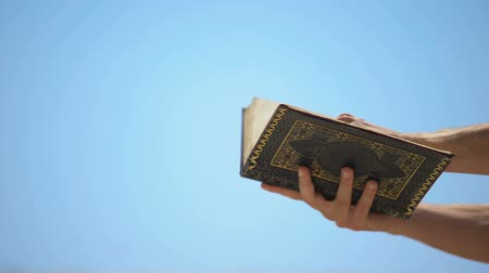 prophète : Male hands holding Koran on sky background, template for islamic inscriptions Vidéos Libres De Droits