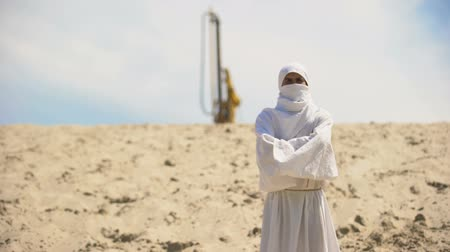beczka : Arab in white clothes standing in desert, oil derrick on backdrop, fuel business Wideo
