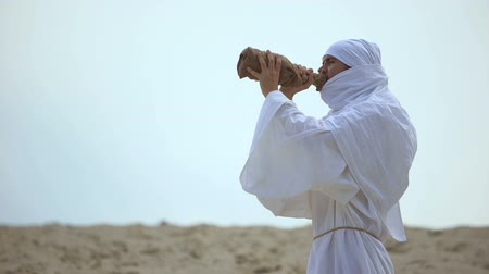 hacı : Thirsty arab pilgrim drinking water from bottle in desert, drought problems Stok Video