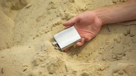 bağımlı : Hand with flask falling lifeless on sand, deadly effects of alcohol addiction Stok Video