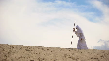 metáfora : Tired Arab falling on sand in desert, concept of difficulties on road to success