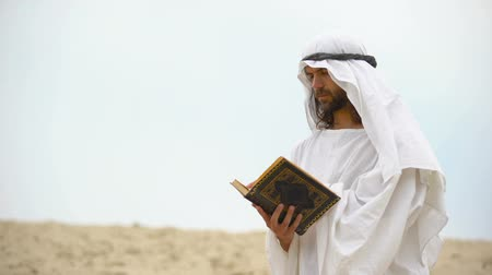 redemption : Arab reading Koran in desert, meditating and reflecting on Muhammad teachings