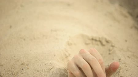 buried : Hand desperately waving, sinking in quicksand, trapped tourist in desert, danger Stock Footage